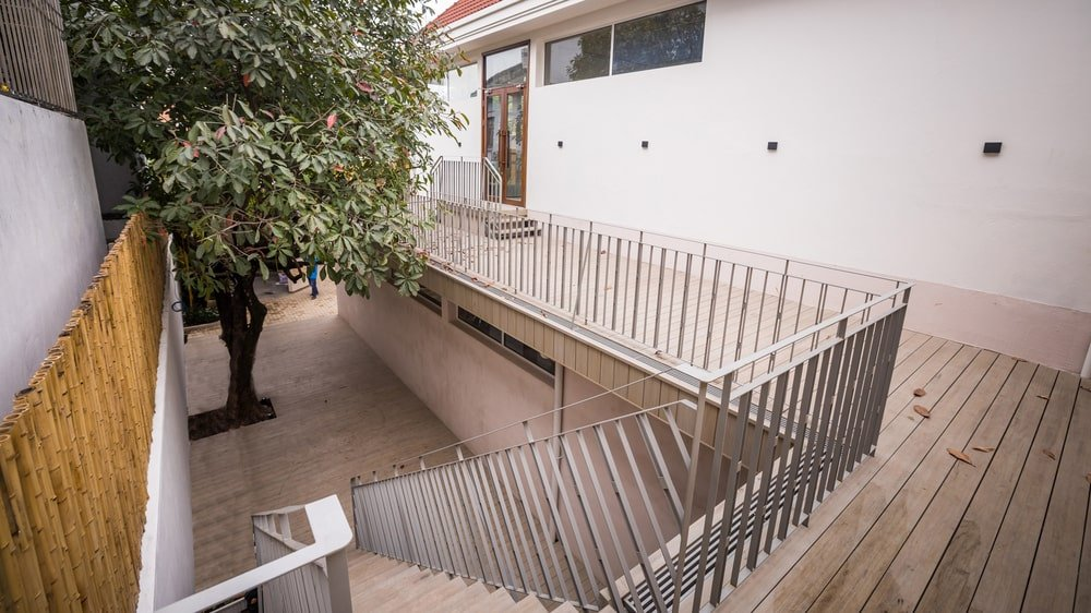 This outdoor staircase leads to this wrap-around terrace balcony with a walkway bordered by railings.