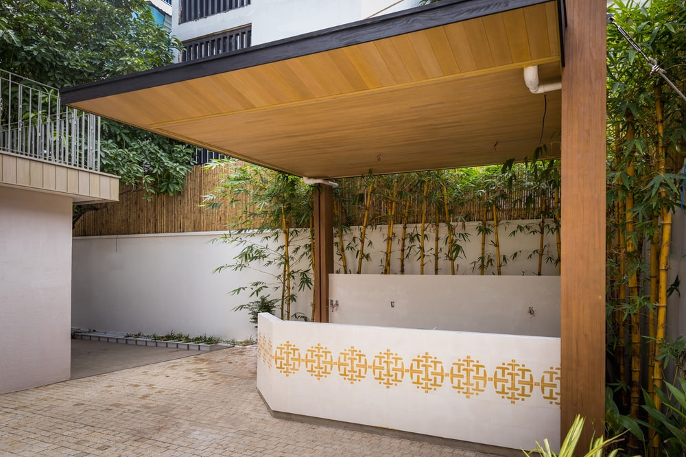 This is a close look at a covered cabana with a tall wooden ceiling and plants in the background.