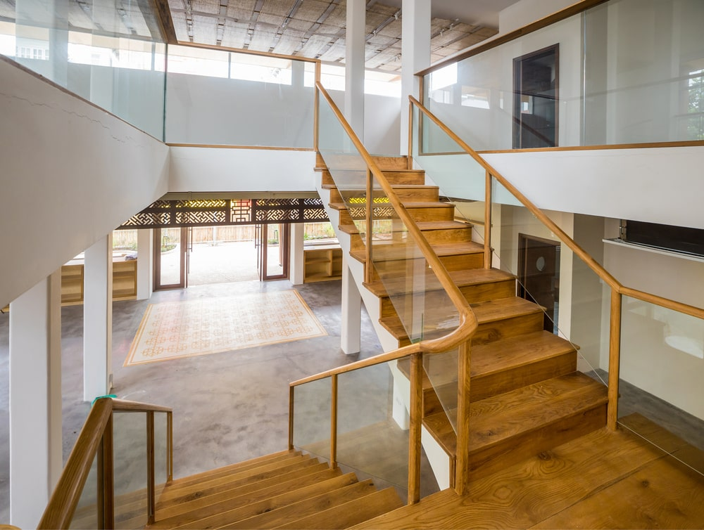 From the foyer is this wooden staircase with glass walls on the side topped with wooden banisters to match the wooden steps.