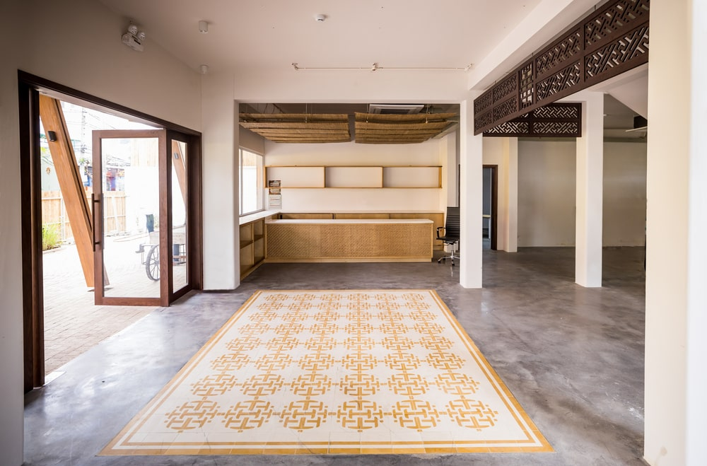 Upon entry of the house, you are welcomed by this simple and spacious foyer that has a yellow patterned area rug and bright natural lighting from the glass doors.