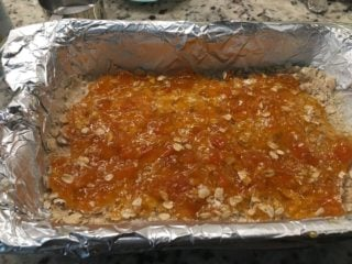 The mixed ingredients are then arranged on the baking pan and topped with apricot preserves.