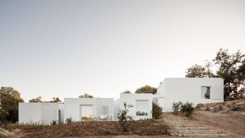 This is a full view of the adobe house with white exterior walls and large entryways complemented by the landscaping of shrubs and stone walkways.