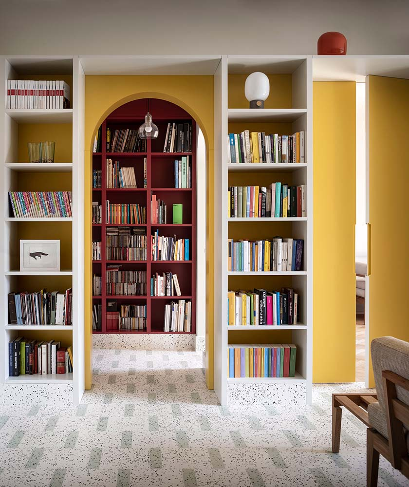 This is a close look at the walls of the house with built-in bookshelves and arches that blend together with the bight yellow walls.