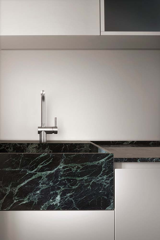 This is a close look at the dark marble sink of the kitchen that matches with the countertop.