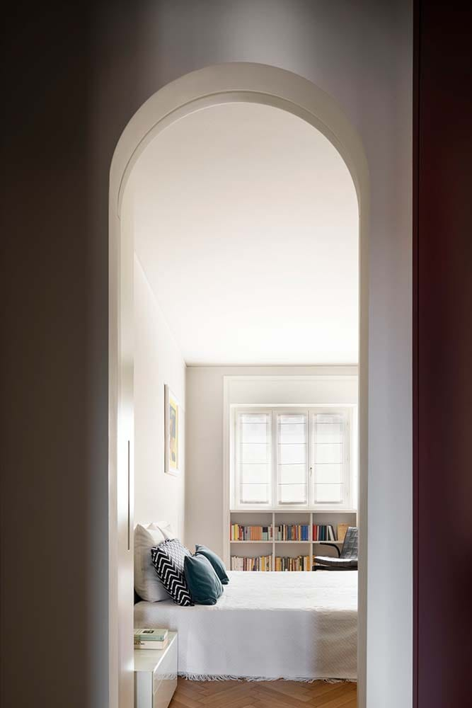 This is another arched entryway that leads to the bedroom with a alrge bed and built-in bookshelf on the far side.