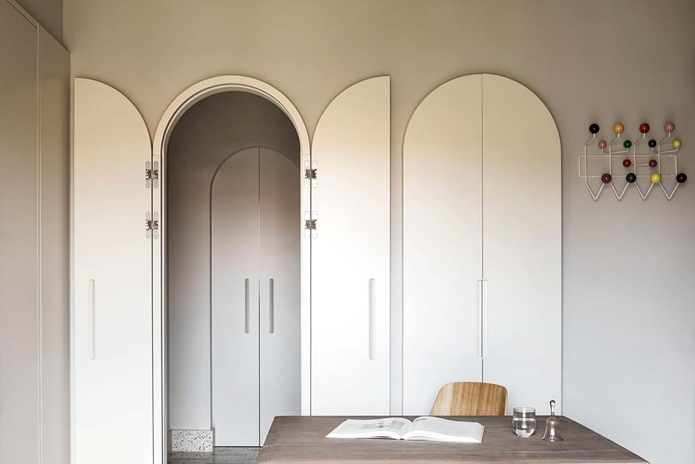 This is a look at the home office with a couple of arched entryways and arched doors that open to the large desk.