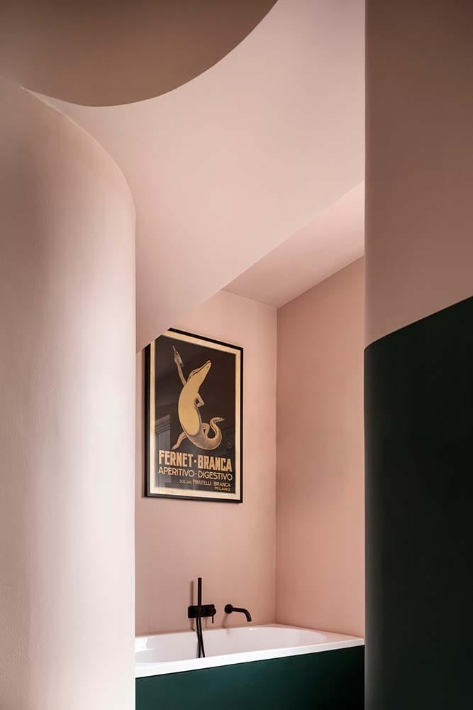 This is a look at the bathroom with pink walls and a wall-mounted artwork above the bathtub.