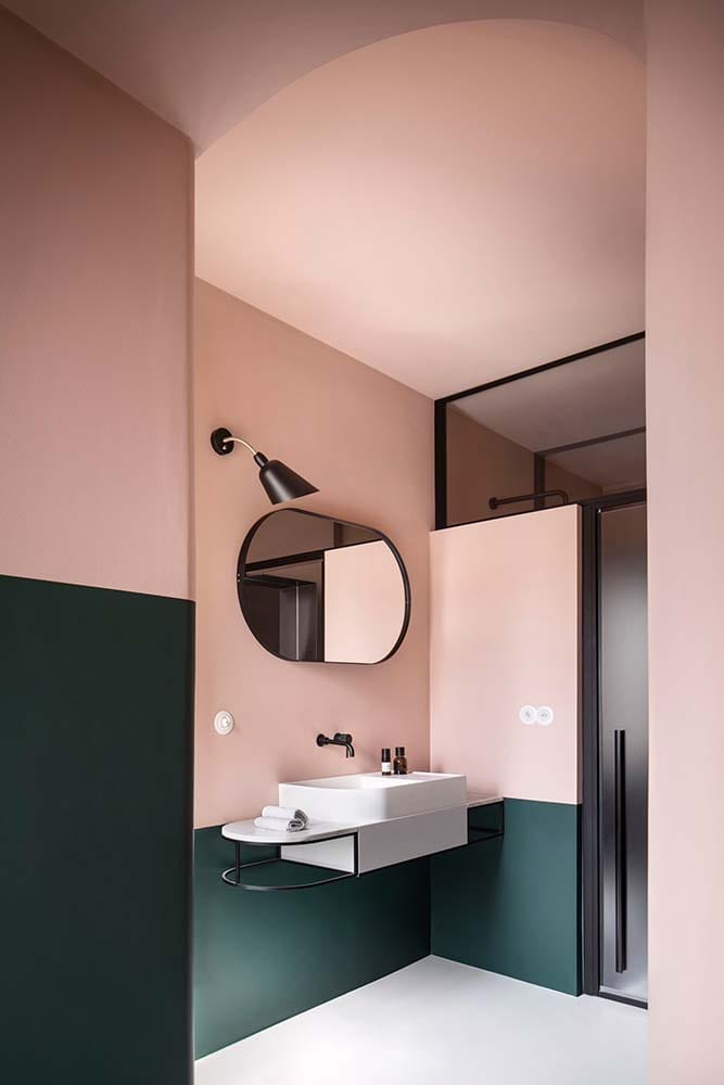 On the other side of the bathroom is the floating sink that is topped with a wall-mounted mirror.