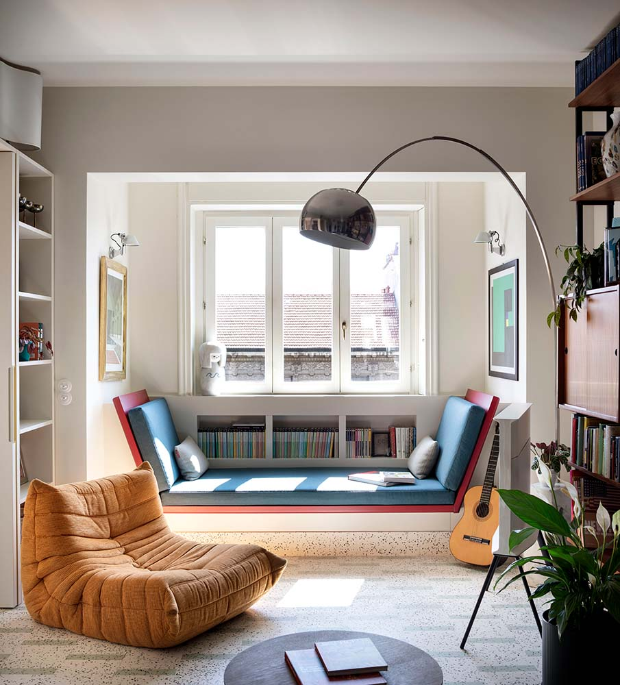 This is a look at the living room that has a cushioned reading nook on the far side by the window with built-in miniature bookshelf under the window.
