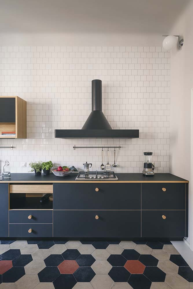 This is a look at the structure of the kitchen that has dark drawers and a dark vent hood that stands out against the white subway tiles.