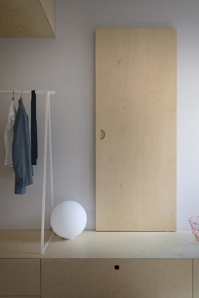 This is a close look at the low wooden structure on the side of the bed with a door decoration, a spherical light and a clothes rack.