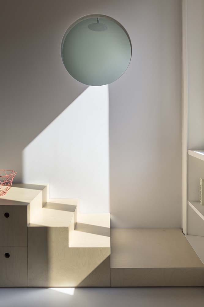 This is the bottom of the wooden set of steps topped with a large spherical pendant light.