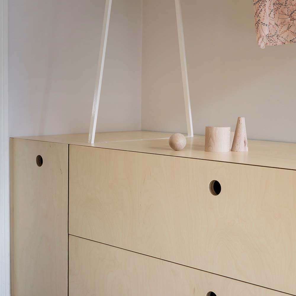 This is a close look at a corner that has a wooden built-in waist-high cabinet with modern handles.