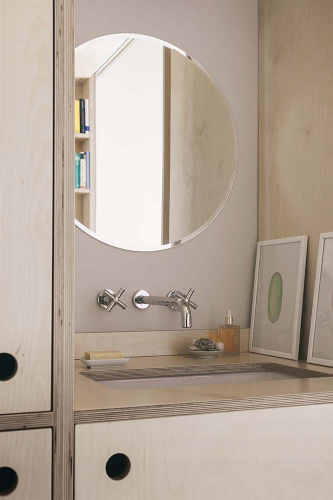 This is a close look at the sink of the bathroom housed in a large wooden structure topped with a round mirror.