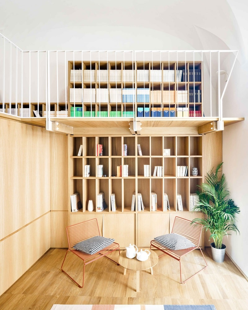 This is a full view of the loft above with wooden bookshelves and the area below that has bookshelves and a reading area.