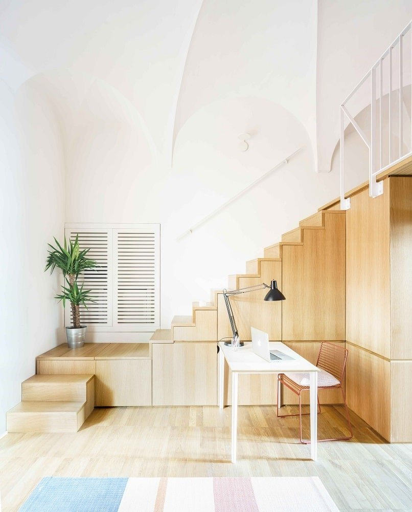 This is the view of the other side that has a white desk beside the modern wooden staircase adorned with a potted plant.