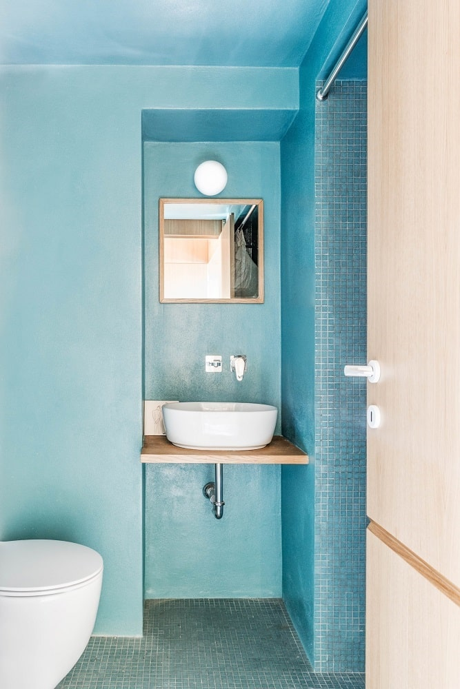 This is the powder room with a blue green tone to its walls that make the toilet and sink stand out.
