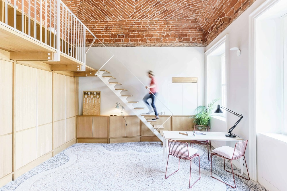 This other angle showcases the modern staircase on the far side by the set of waist-high wooden cabinets.