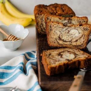 A sliced loaf of cinnamon swirl banana bread on a chopping board.