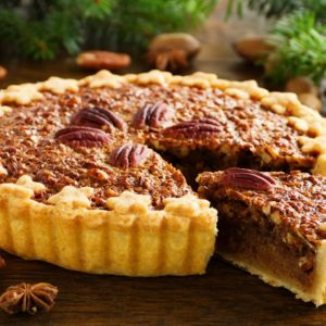 A full pecan pie with a slice.