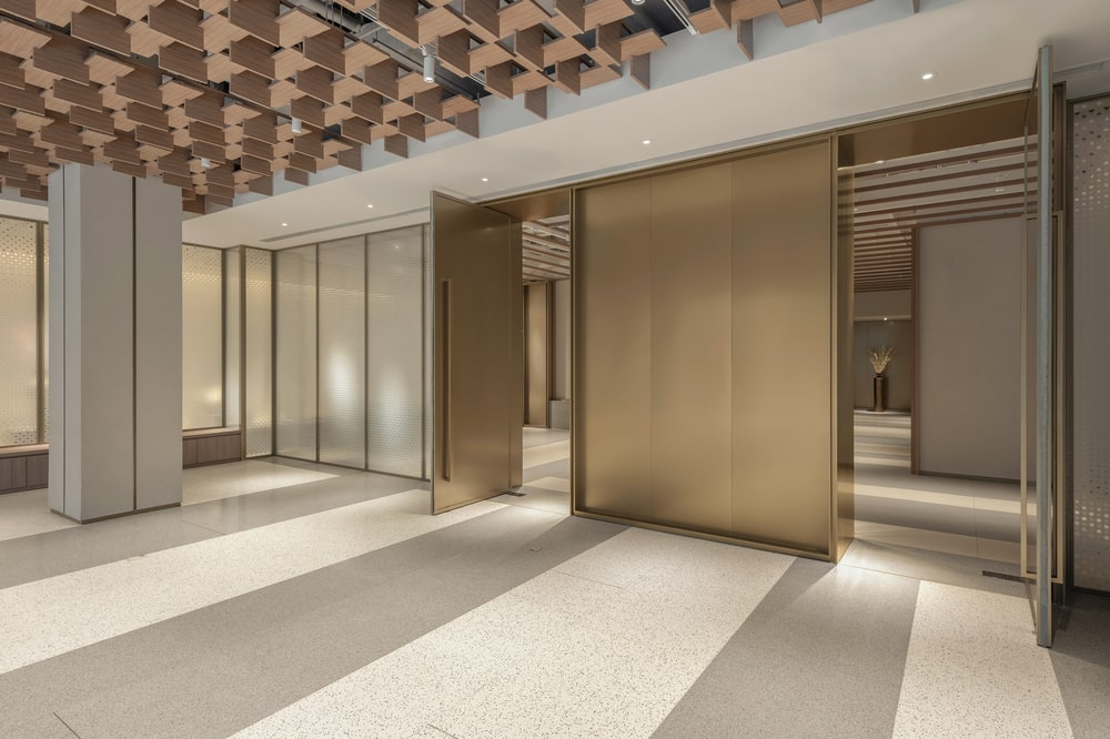 This is an interior look that showcases striped flooring, wooden panels on the ceiling and sleek brass doors.