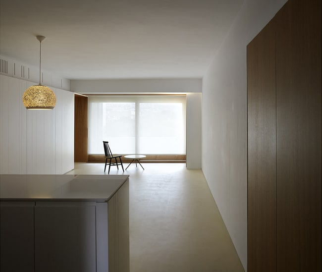 This is a view of the large room from the vantage of the kitchen island with a large glass wall on the far side.