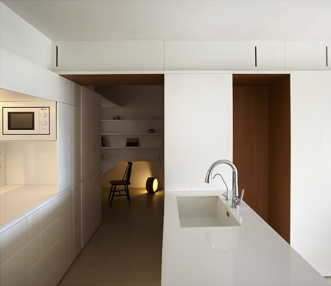The kitchen has a bright white kitchen peninsula that houses the sink.