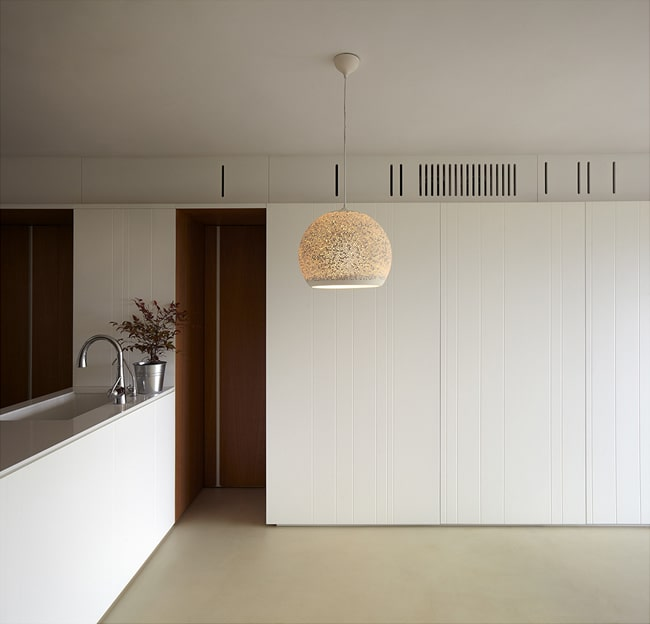 This is a look at the dining and living room beyond the kitchen peninsula that has a dome pendant light.