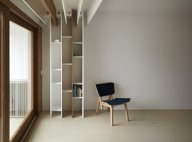 This is a close look at the wall by the large glass window that has built-in wooden bookshelves.