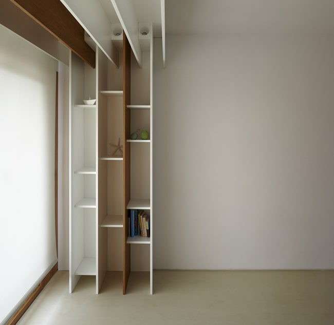 The built-in wooden bookshelves have a unique design that extends to the ceiling.
