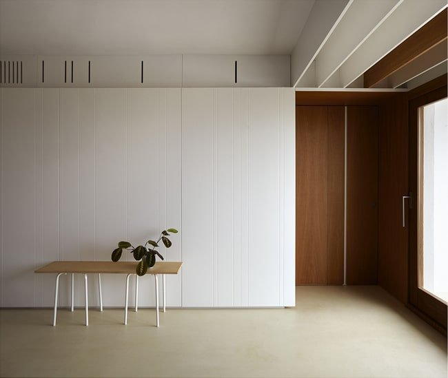 This is the white wall on the side of the large area with built-in cabinets topped with a white tray ceiling.