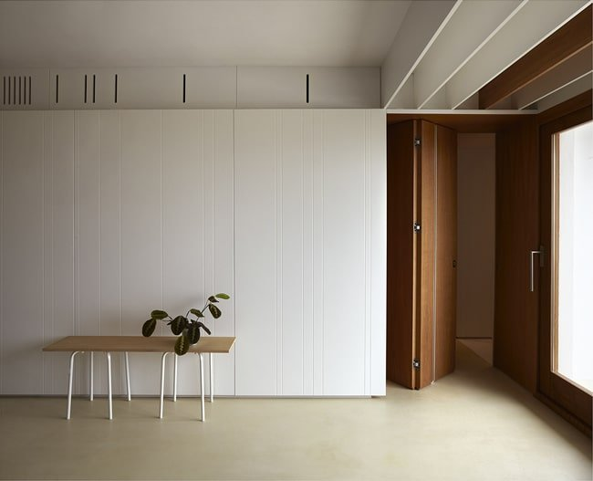 On the side of the large built-in cabinets is a set of wooden folding doors.