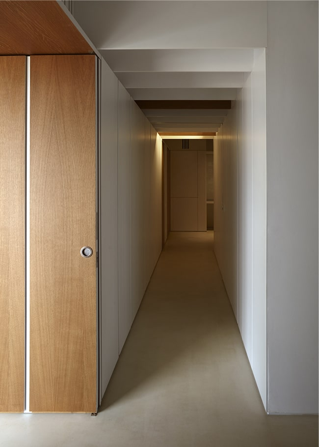 The set of wooden folding doors open to this long and narrow hallway with warm lighting.