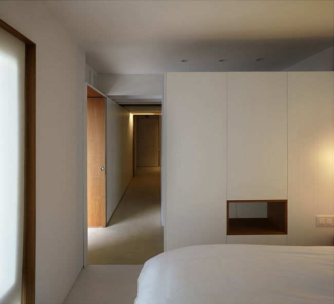 On the other side of this long hallway is the bedroom with white walls and ceiling.