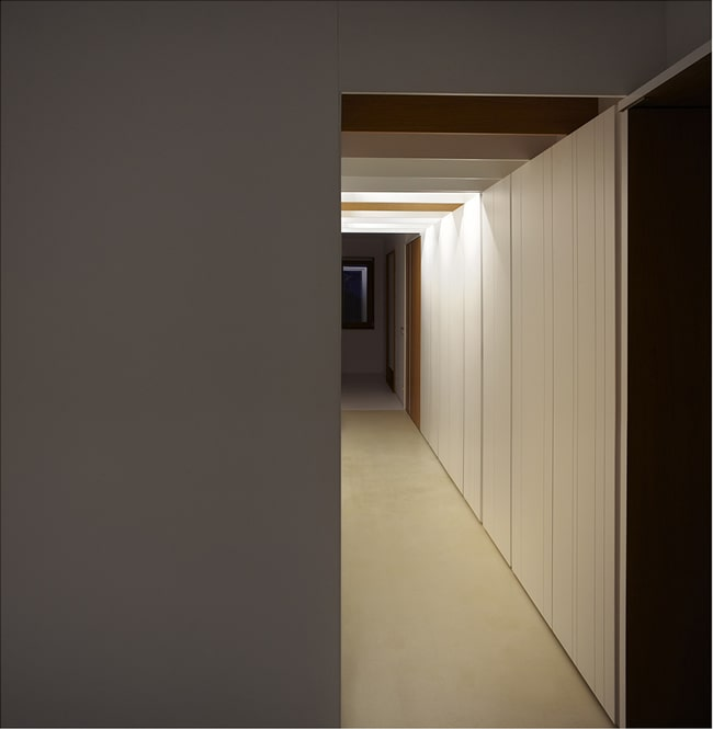 This is another look at the long and narrow hallway of the house with warm lighting and white walls.