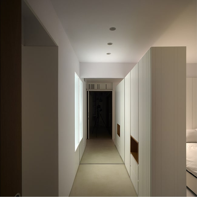 The white walls and white ceiling of the hallway are also complemented by the bright natural lights coming from the window.