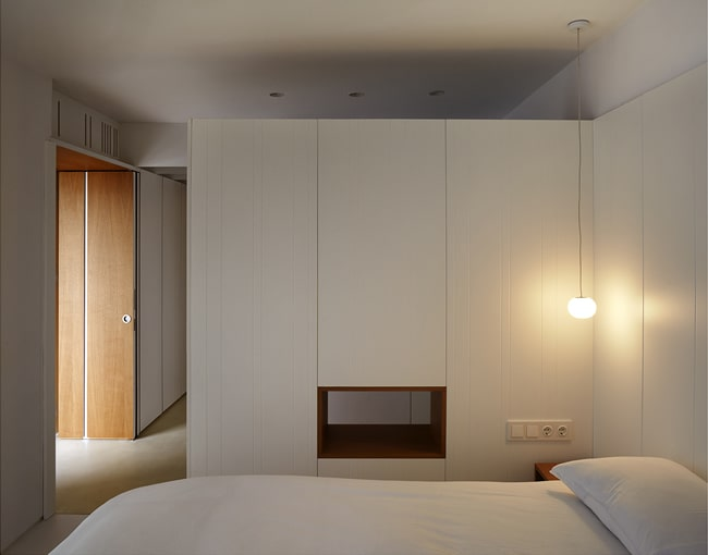 This is another look at the bedroom that has a white wall and a small window on the bottom part of the wall beside the bed along with a simple pendant light.