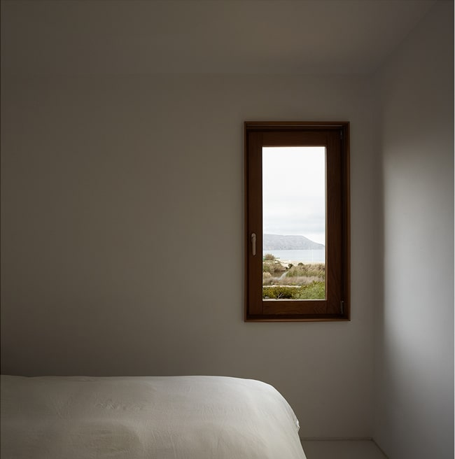 On the other wall of the bedroom is a small rectangular window that shows a view of the outdoors and lets in natural lighting.