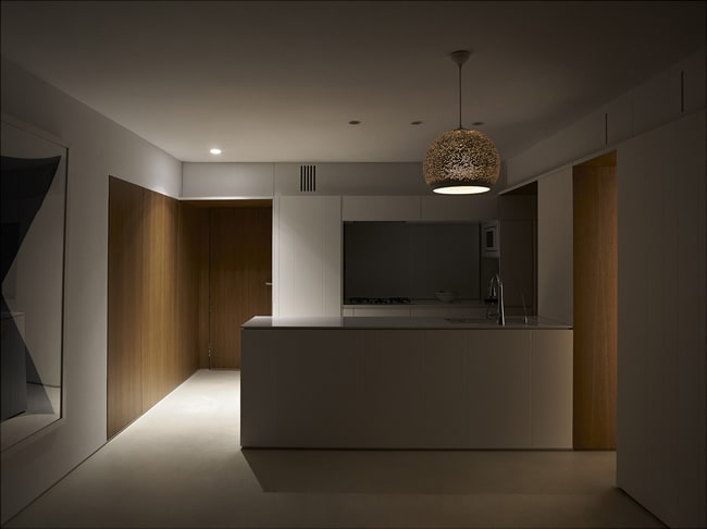 This is a view of the kitchen when the lights are off showcasing the light of the pin lights and dome pendant light.