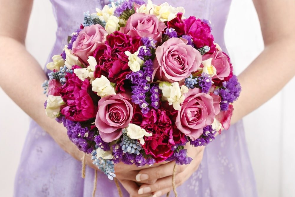 A close look at a woman holding a bouquet of flowers.