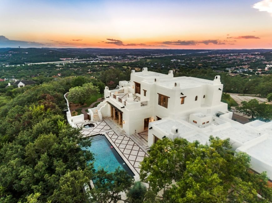 This is an aerial view of the mansion with bright white adobe exterior walls complemented by the large pool and the surrounding thick green landscaping of tall trees. Image courtesy of Toptenrealestatedeals.com.