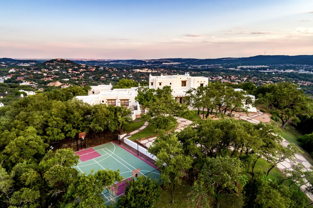 This is an aerial view of the property showcasing the white adobe mansion, the tennis court and the lush landscaping of tall trees that complement them. Image courtesy of Toptenrealestatedeals.com.