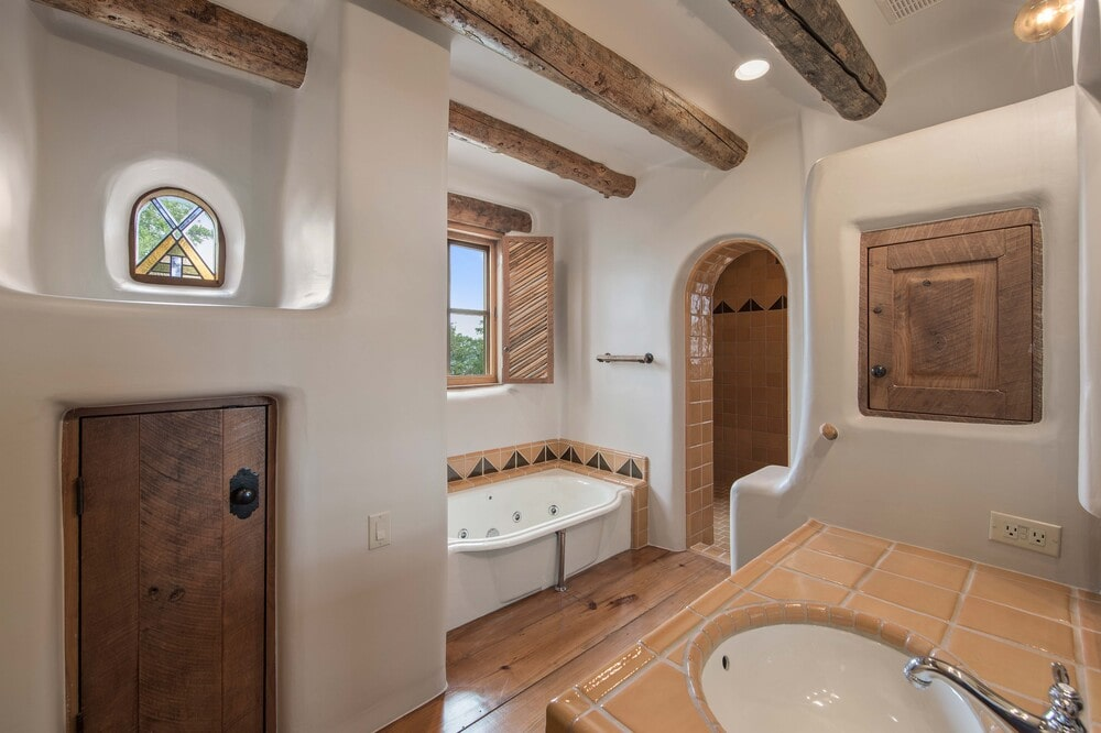 The bathroom has a bathtub under the windows by the arched entryway leading to the walk-in shower area. Image courtesy of Toptenrealestatedeals.com.