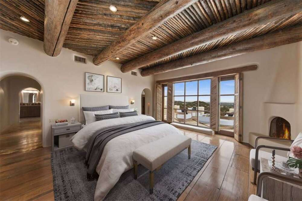 The primary bedroom has a wooden ceiling that has log beams exposed over the bed that is adorned by its gray area rug and cushioned bench at the foot. Image courtesy of Toptenrealestatedeals.com.
