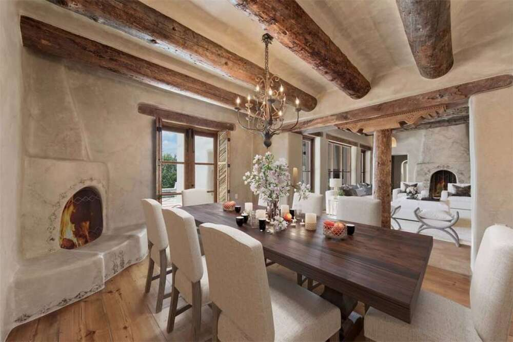 The formal dining room has exposed wooden log beams at the ceiling to match the long rectangular dining table surrounded by cushioned chairs that match the walls. Image courtesy of Toptenrealestatedeals.com.
