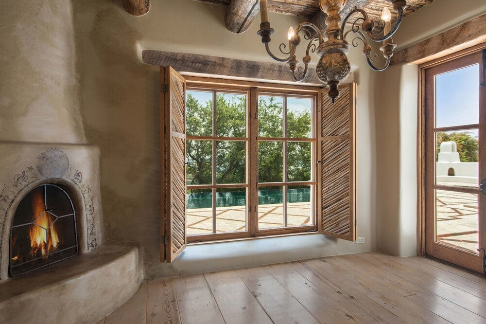 This is an open area that has lots of natural lighting coming in from the glass windows and doors. These are then complemented by the chandelier and fireplace at the corner. Image courtesy of Toptenrealestatedeals.com.
