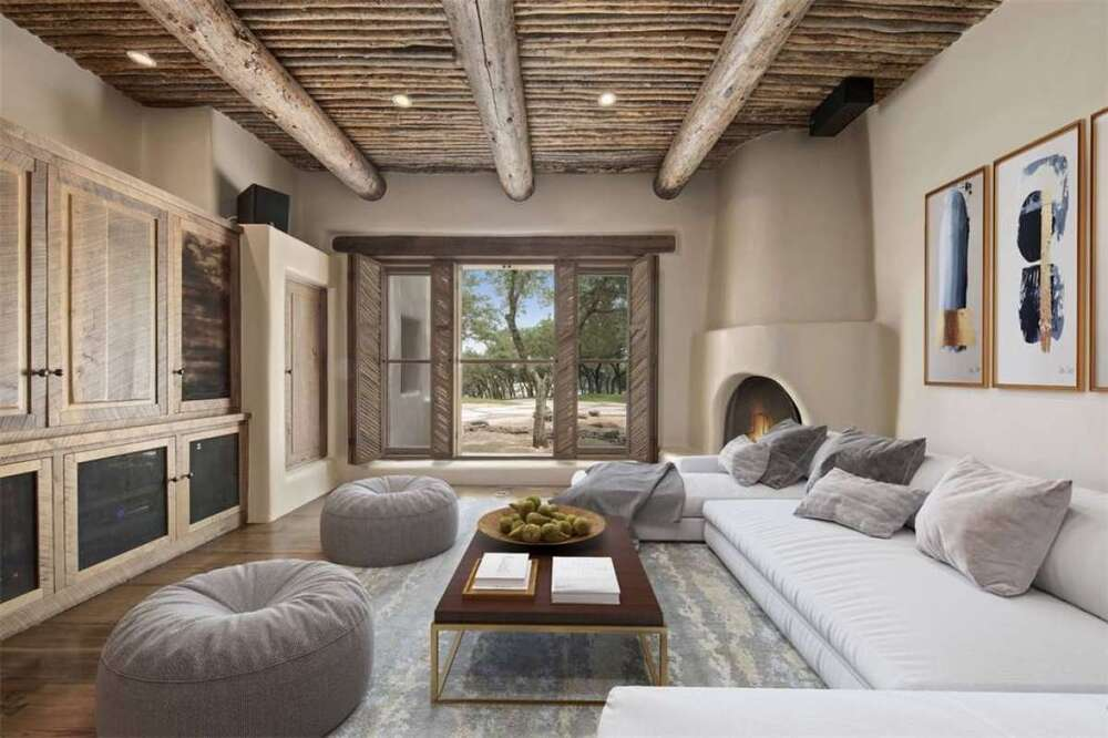 The family room has a large U-shaped light gray sectional sofa against the wall across from a large wooden structure that matches the wooden ceiling with exposed beams. Image courtesy of Toptenrealestatedeals.com.