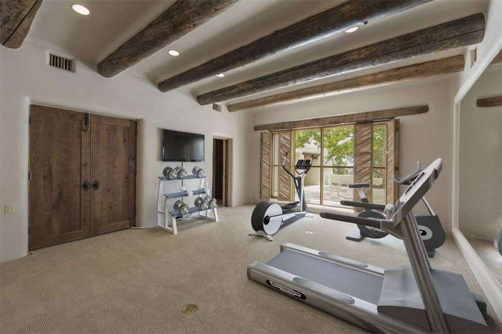 The spacious home gym has various cardio machines and weights under a large ceiling that has exposed wooden beams. Image courtesy of Toptenrealestatedeals.com.