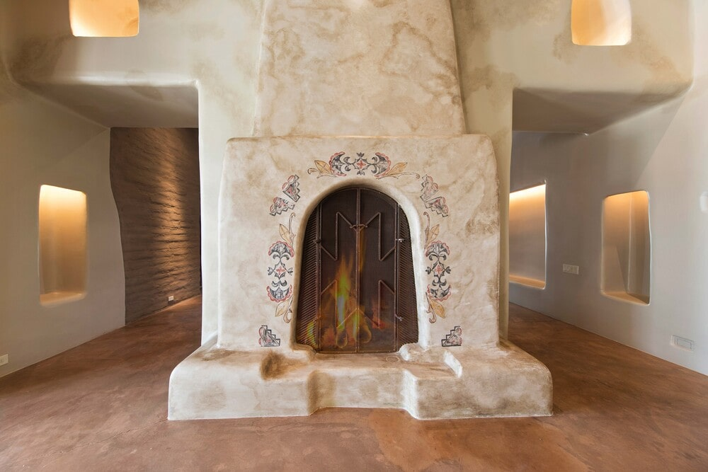 This is a close look at the large adobe fireplace at the hallway with a large arch and textured surfaces. Image courtesy of Toptenrealestatedeals.com.