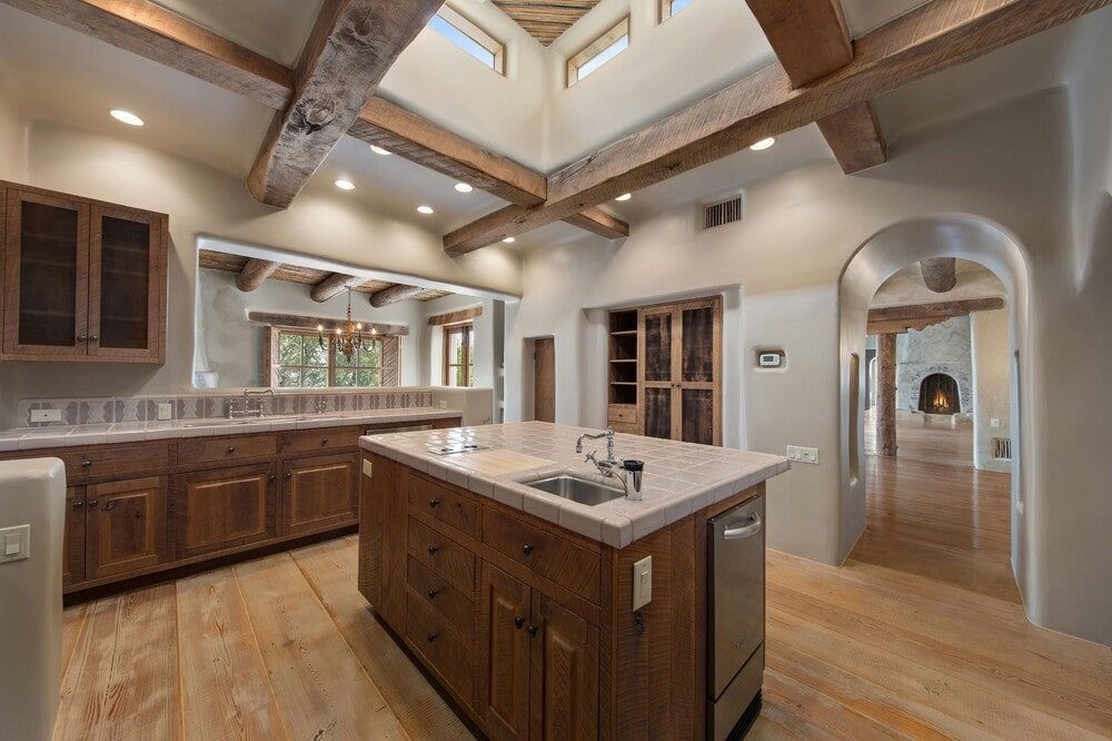 This is the kitchen that has a large kitchen island in the middle with brown wooden cabinetry that matches those lining the walls and the exposed beams of the ceiling. Image courtesy of Toptenrealestatedeals.com.